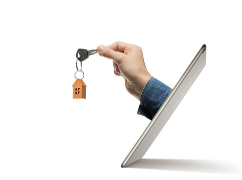 Key with paper house in human hand stick out of a digital tablet screen. Concept of modern technologies in real estate industry.