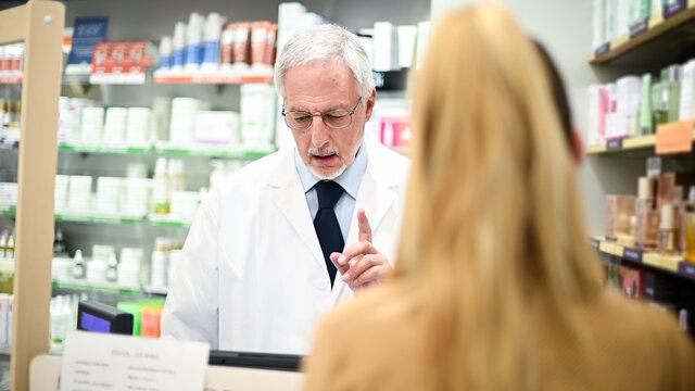 Senior pharmacist dealing with a customer
