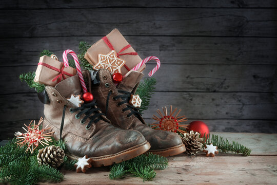 Old hiking boots filled with sweets and Christmas decoration on Nicholas day, or German Nikolaus Tag, 6th December, tradition to put the shoes outside, rustic wooden background with copy space