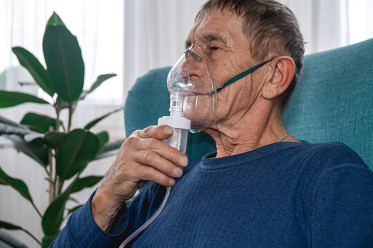 elderly senior sits in a armchair with an oxygen mask in quarantine at home