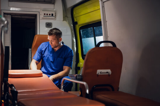 Paramedic on duty, driving to his patient in an ambulance car, raining outside.
