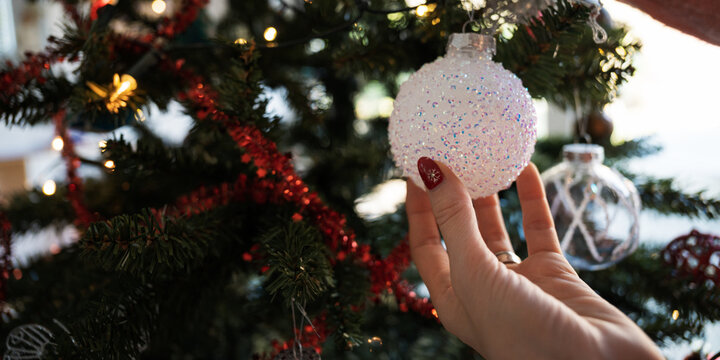 Placing shiny white bauble on christmas tree