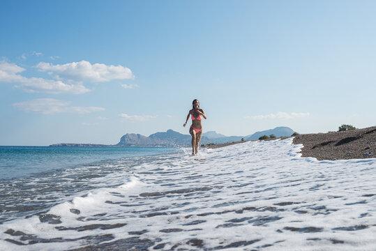 Young woman in pink bikini running alongside beautiful pebble beach