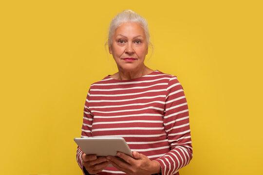 Senior hispanic woman reading news on screen of tablet