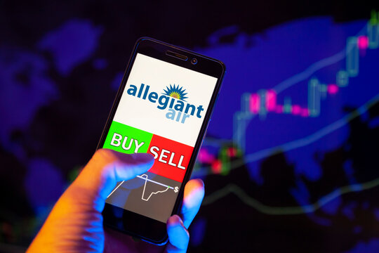 logo ALLEGIANT TRAVEL COMPANY (ALGT) on smartphone screen, hand of trader holding mobile phone showing BUY or SELL on background of stock chart. Russia, Stavropol - May 29, 2019
