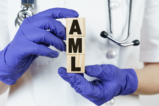 The doctor holds cubes in his hands on which it is written - AML. Acute Myeloid Leukemia
