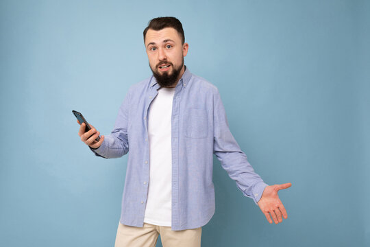 surprised young man with a phone in his hands against a background of a blue wall.