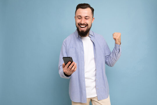 Portrait of an excited young man looking at mobile phone isolated over blue background, celebrating