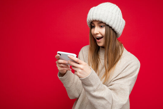 Image of a shocked young beautiful woman posing isolated over red wall background play games by mobile phone.