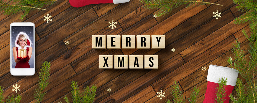 cubes with message MERRY XMAS and smartphone showing a Miss Santa on wooden background