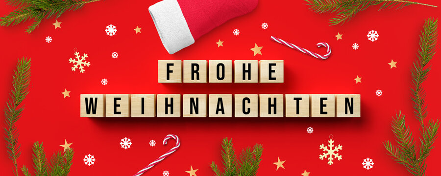 cubes with German message for MERRY CHRISTMAS and christmas decoration on red background