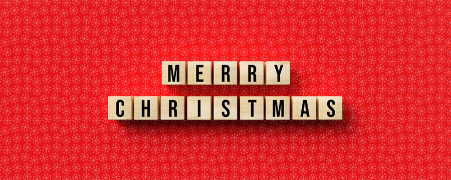 cubes with message MERRY CHRISTMAS and christmas decoration on red background