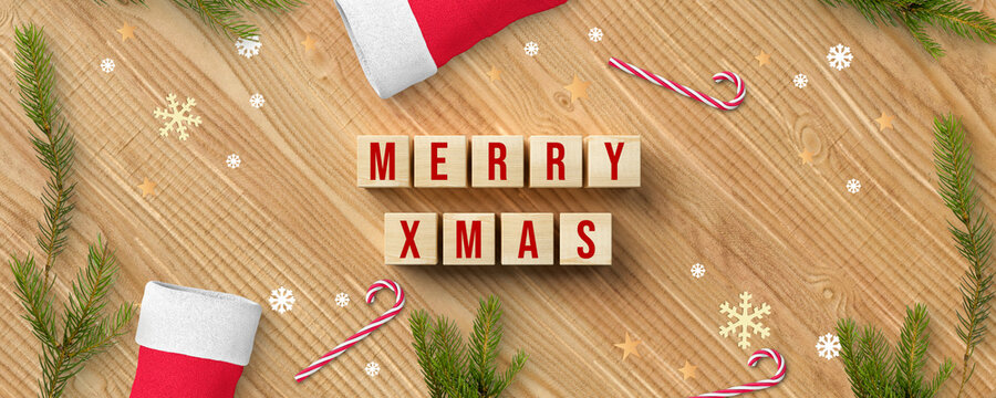 cubes with message MERRY XMAS and christmas decoration on wooden background