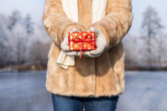 Woman holding christmas present in snowy landscape. Small red gift box in female hands