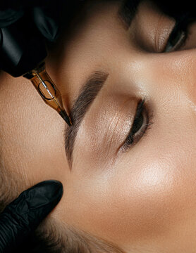 Woman in gloves applying brow tattoo