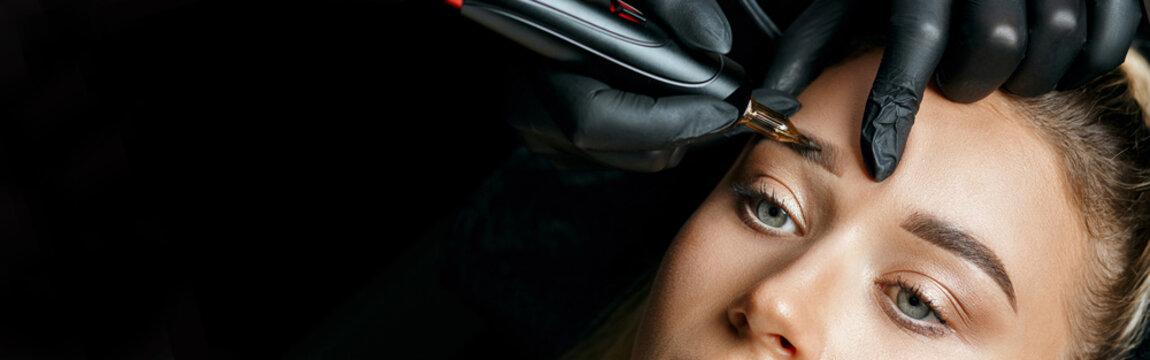 Tattoo artist doing permanent makeup
