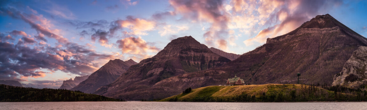 Iconic Hotel in Glacier Lake surrounded by the beautiful Canadian Rocky Mountains during a cloudy summer sunset. Taken in Upper Waterton Lake, Alberta, Canada.