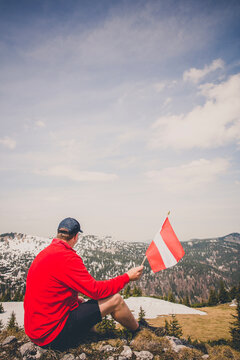 Side View Of Man Holding Austrian Flag While Sitting On Mountain Against Sky During Winter