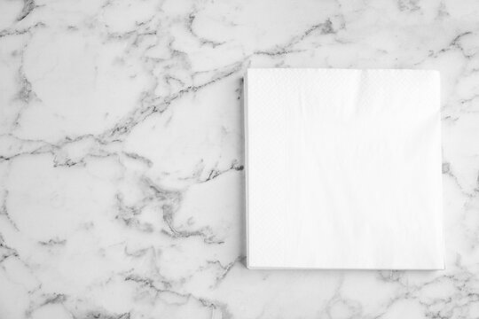 Stack of clean paper tissues on white marble table, top view. Space for text