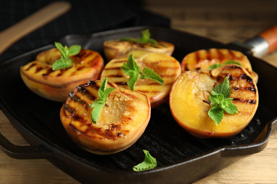 Delicious grilled peaches with mint on table, closeup
