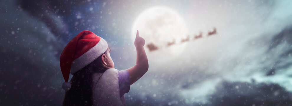 little girl surprised to see Santa Claus on beautiful Christmas night under moonlight