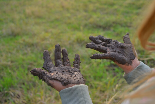 Kid outdoor with muddy hands adventure concept symbol