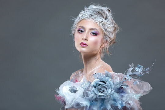 Winter Beauty Woman in clothes made of frozen flowers covered with frost, with snow on her face and shoulders. Christmas Girl Makeup. Make-up the snow Queen. Isolated on a gray background.