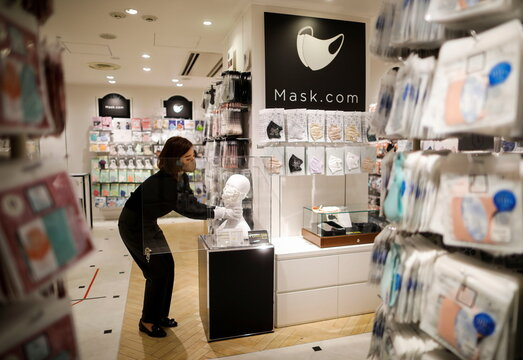 An employee of Cox Co, the operation company of the face-mask speciality shop Mask.com, displays a luxury face mask decorated with the diamond, platinum and Swarovski crystals in Tokyo