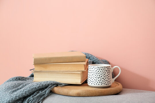 Books, plaid and cup of tea on color background