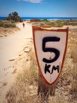 Distance Marker On Beach With Man Walking In Background