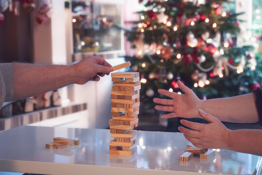 During the Christmas season, the family plays board games together. Woman and man build a wobbly tower from wooden blocks. In the background is the Christmas tree.
