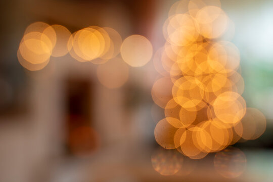 Living room with Christmas tree. Shiny bokeh due to blurring in the whole picture. Christmassy background.