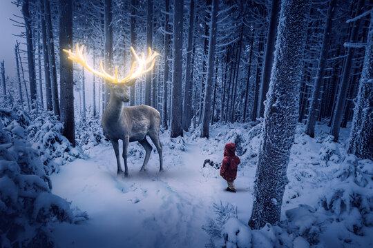 Der Hirsch mit dem goldenen Geweih steht in einer kalten Winternacht vor einem kleinen Kind mit roter Jacke