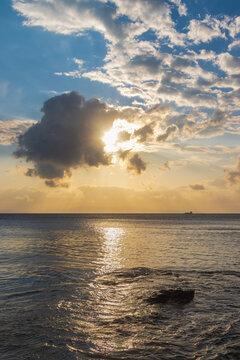 Sonnenuntergang über der griechischen Kykladeninsel Tinos mit der Insel Syros und einem Schiff am Horizont