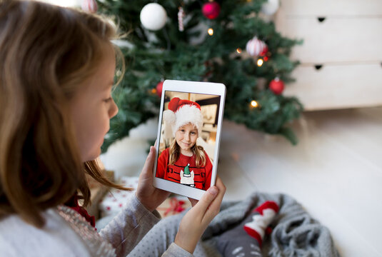 Social distance - Pretty girl on video call with family during Christmas quarantine