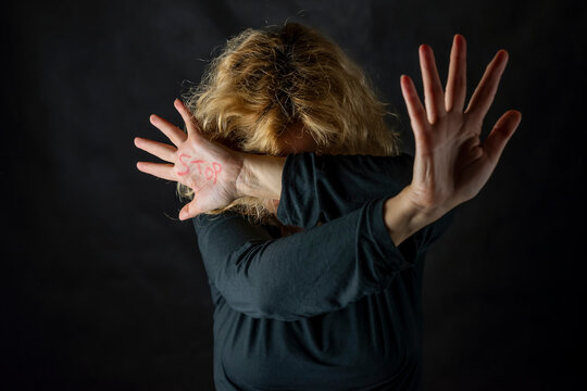 A blonde woman covers her face with a hand on which she has written the word Stop, to stop violence against women