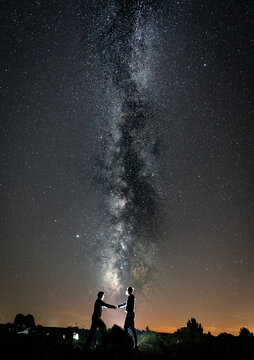 Two persons shaking hands against milky way