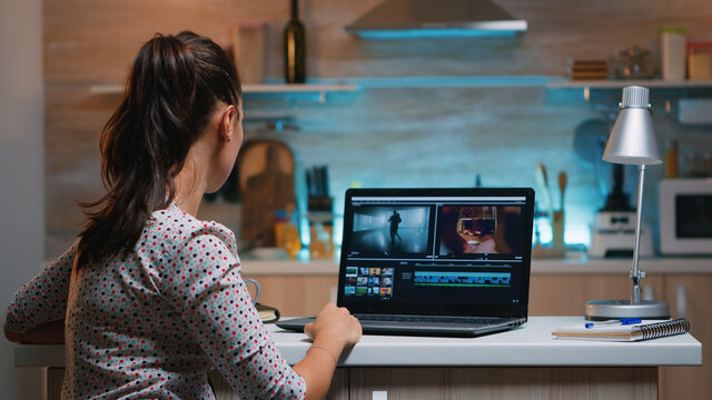 Video editor working from home at night at new project editing audio film montage sitting in modern kitchen. Content creator using professional laptop modern technology network wireless