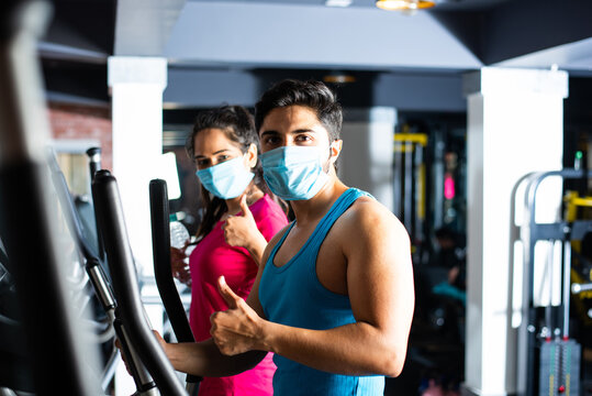 Indian asian young couple wears face mask and working out in the gym