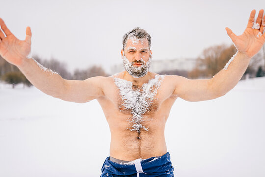 Strong brutal naked man with beard in the snow posing outdoors