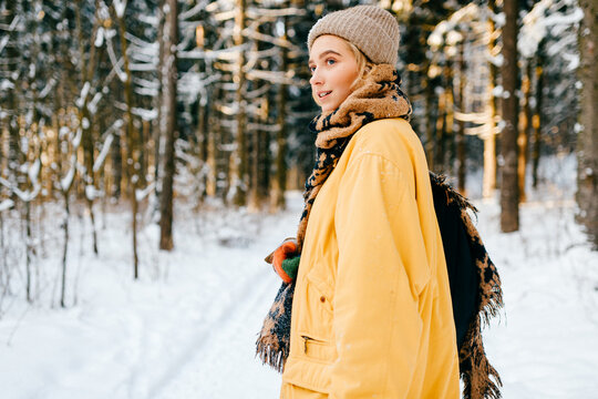 Young stylish hipster girl in yellow jacket with a warm scarf posing in the snow forest