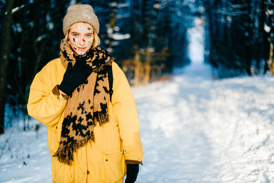 Young stylish hipster girl in yellow jacket and confetti on the face posing in the snow forest