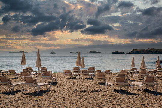 Parasols and deckchairs on empty beach of Ibiza at sunset. Spain