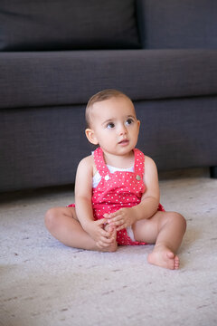 Lovely little baby sitting on carpet barefoot in living room. Cute thoughtful girl in red dungarees shorts looking at someone and touching foot. Weekend, childhood and being at home concept