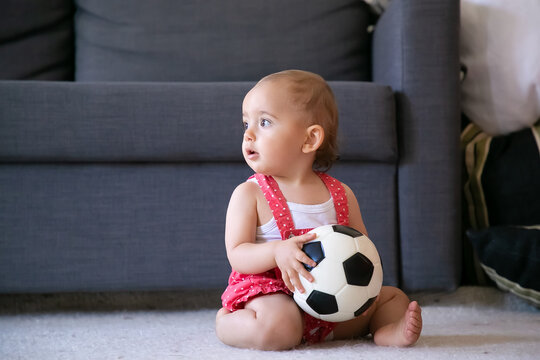 Adorable baby girl holding soccer ball, sitting on carpet barefoot and looking away. Cute infant in red dungarees shorts playing at home alone. Holiday, weekend and childhood concept