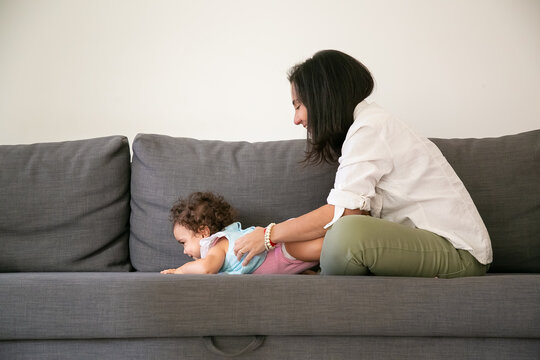 Happy black haired mom cuddling cute baby daughter on grey couch. Side view. Parenthood and childhood concept