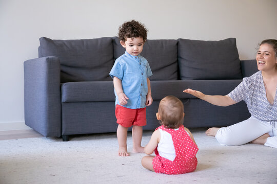 Serious mix-raced boy standing and looking at baby. Caucasian pretty mom talking something to children, smiling and playing with kids at home. Family indoors, weekend and childhood concept