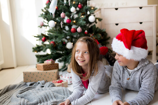 Girl and boy lying in front of a Christmas tree celebrating Christmas
