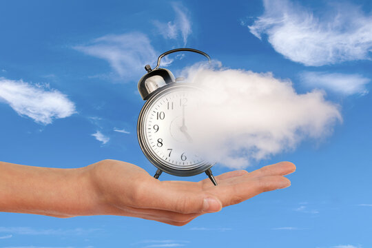 Hand holding a clock dissolving away in a cloud. Time flies, time management concept. Surreal collage.
