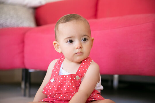 Pensive baby sitting on floor in living room and thinking about something. Serious little girl in red dungarees shorts looking away and sitting near sofa. Weekend, childhood and being at home concept